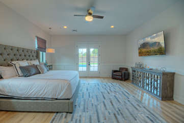 Primary suite with doors to pool is ready for sweet dreams or watching large television