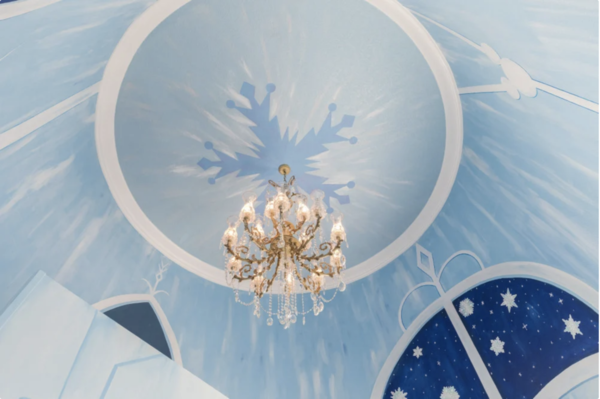 A crystal chandelier hangs over the Ice Princess-inspired kids bedroom