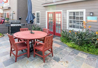 Front patio with grill, umbrella covered table and seating for 5.