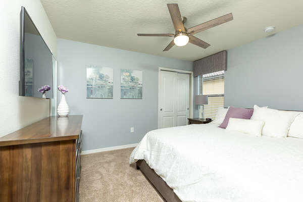 Upstairs bedroom with a king sized bed, large TV and a pop of purple color