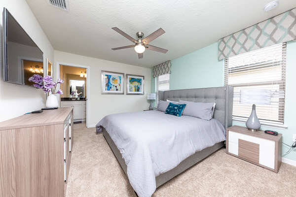 A large upstairs master bedroom with TV and en-suite bathroom