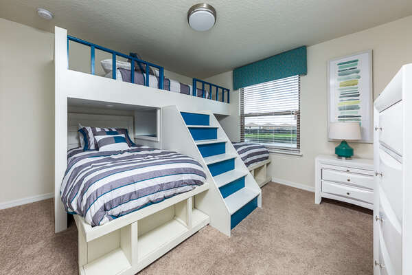 An upstairs kid`s bedroom with three twin beds in a custom build bunk bed