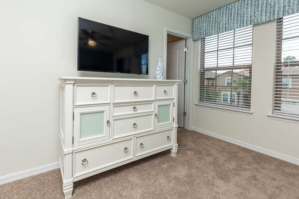 A large TV and spacious storage cabinet in the bedroom
