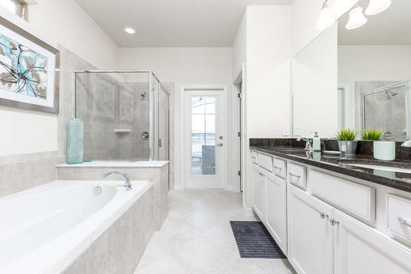 The en-suite master bathroom features dual sinks, a bathtub, walk-in shower and access to the pool area