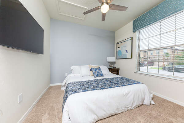 A first floor bedroom with a king sized bed and large TV