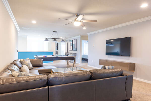A comfy couch and large TV in the upstairs loft