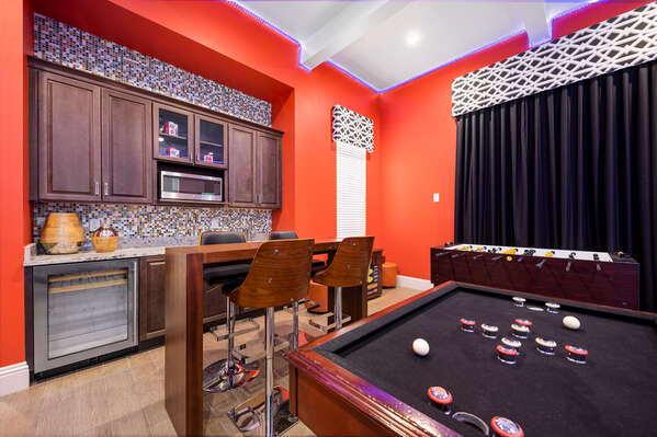 The arcade room bar is perfect for preparing your favorite snacks and drinks to enjoy at the 4-seater hightop table