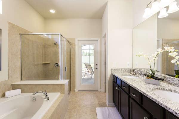 Master en-suite bathroom with patio access, walk-in shower, and garden tub