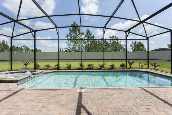 Enjoy your private screened-in pool with spillover spa