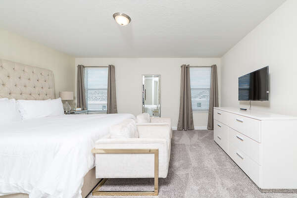 The upstairs master bedroom with a King sized bed, seating and a TV