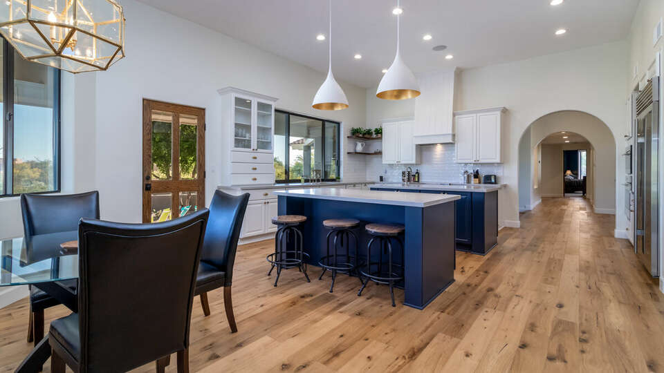 Full, modern kitchen with two islands, bar seating and a dining area.