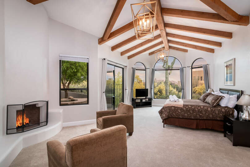 Stunning primary bedroom with wood-beamed, vaulted ceiling.