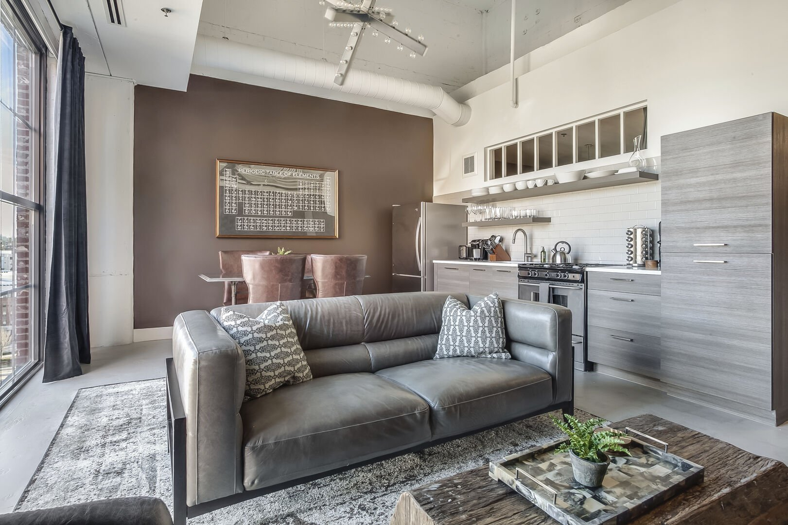 Living Area with Gray Leather Sofa at Ponce City Market Apartment