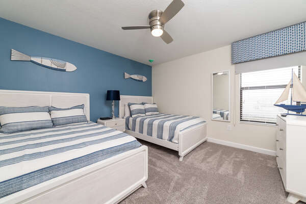 Nautical bedroom features a full and twin bed