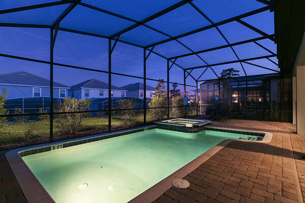 Enjoy your evening by the screened-in private pool with spillover spa