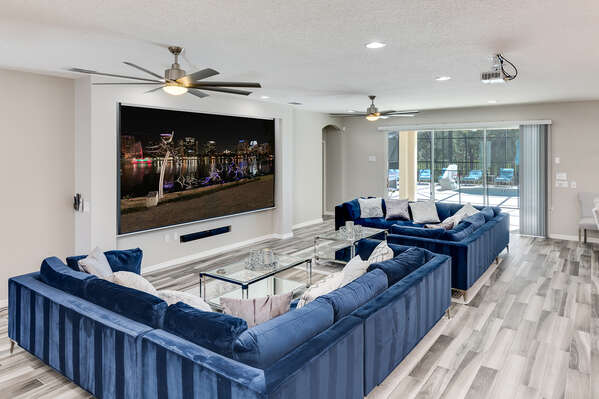 150-inch projector screen comes down in front of the TV to watch movies in the evening
