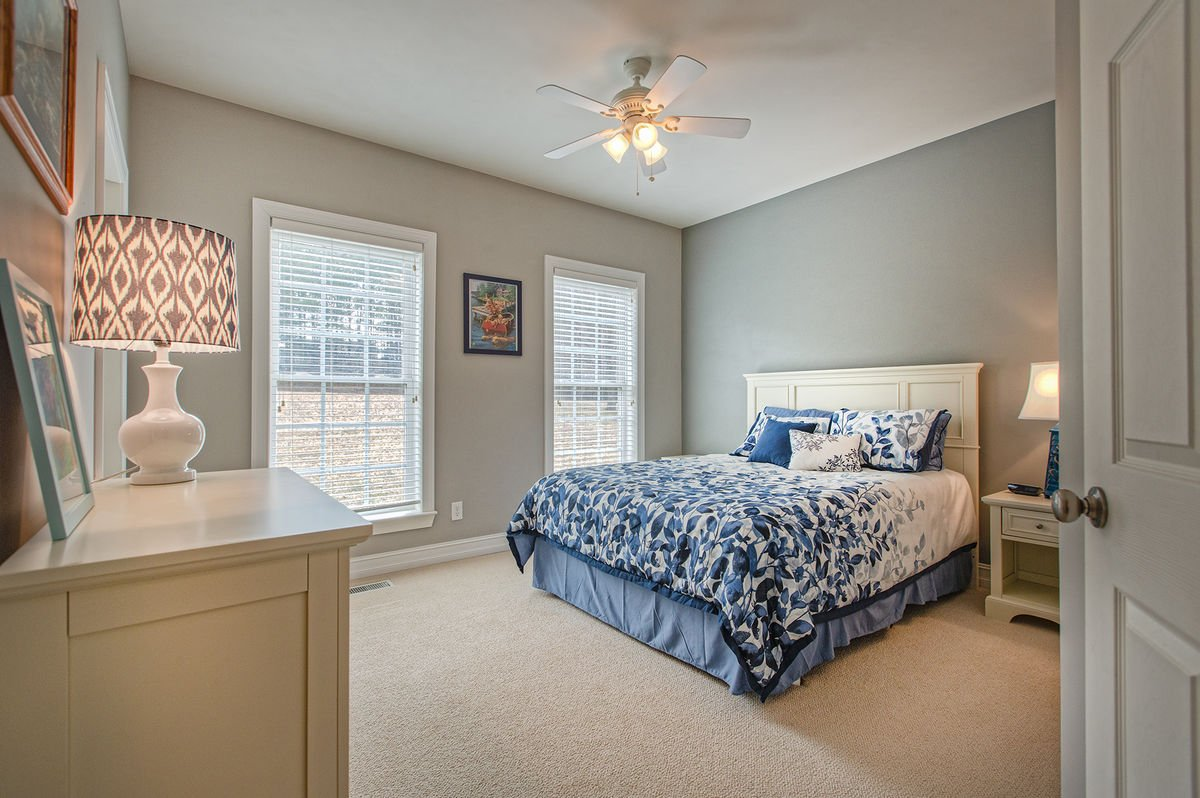 Guest Bedroom with Queen Bed and Large Windows