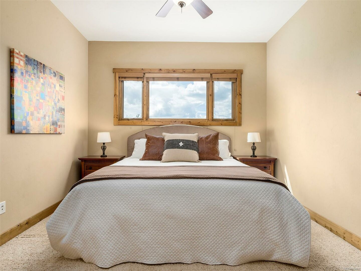 Bedroom with Large Bed, Window, Nightstands, Table Lamps, and Ceiling Fan.