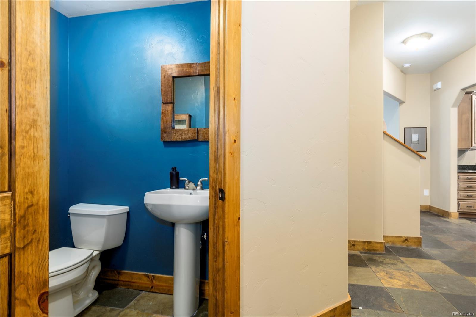 Lower Level Bathroom, Pedestal Sink, Mirror, and Toilet.