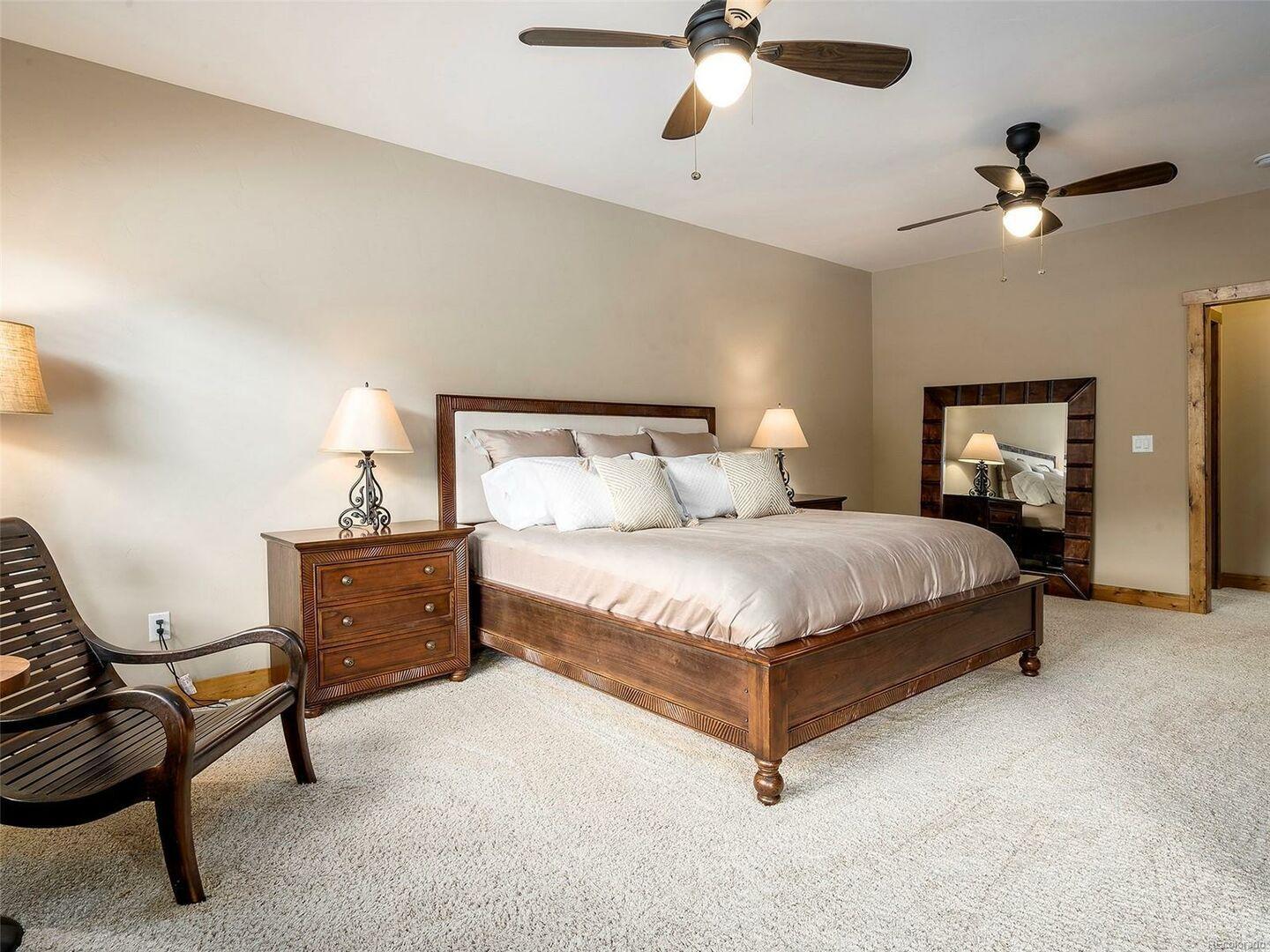 Bedroom with Large Bed, Nightstands, Ceiling Fans, and Chair.