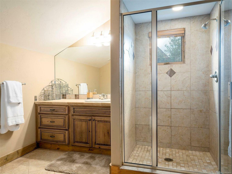 Walk-In Shower, Single Sink Vanity, and Mirror.