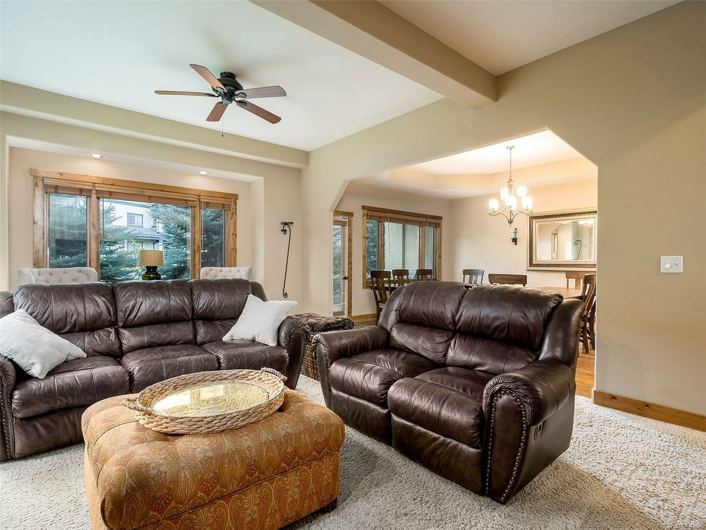 Living Area with Two Sofas, Coffee Table, Ceiling Fan, and Windows.