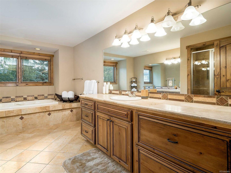 Single Sink Vanity, Mirror, and Hot Tub.