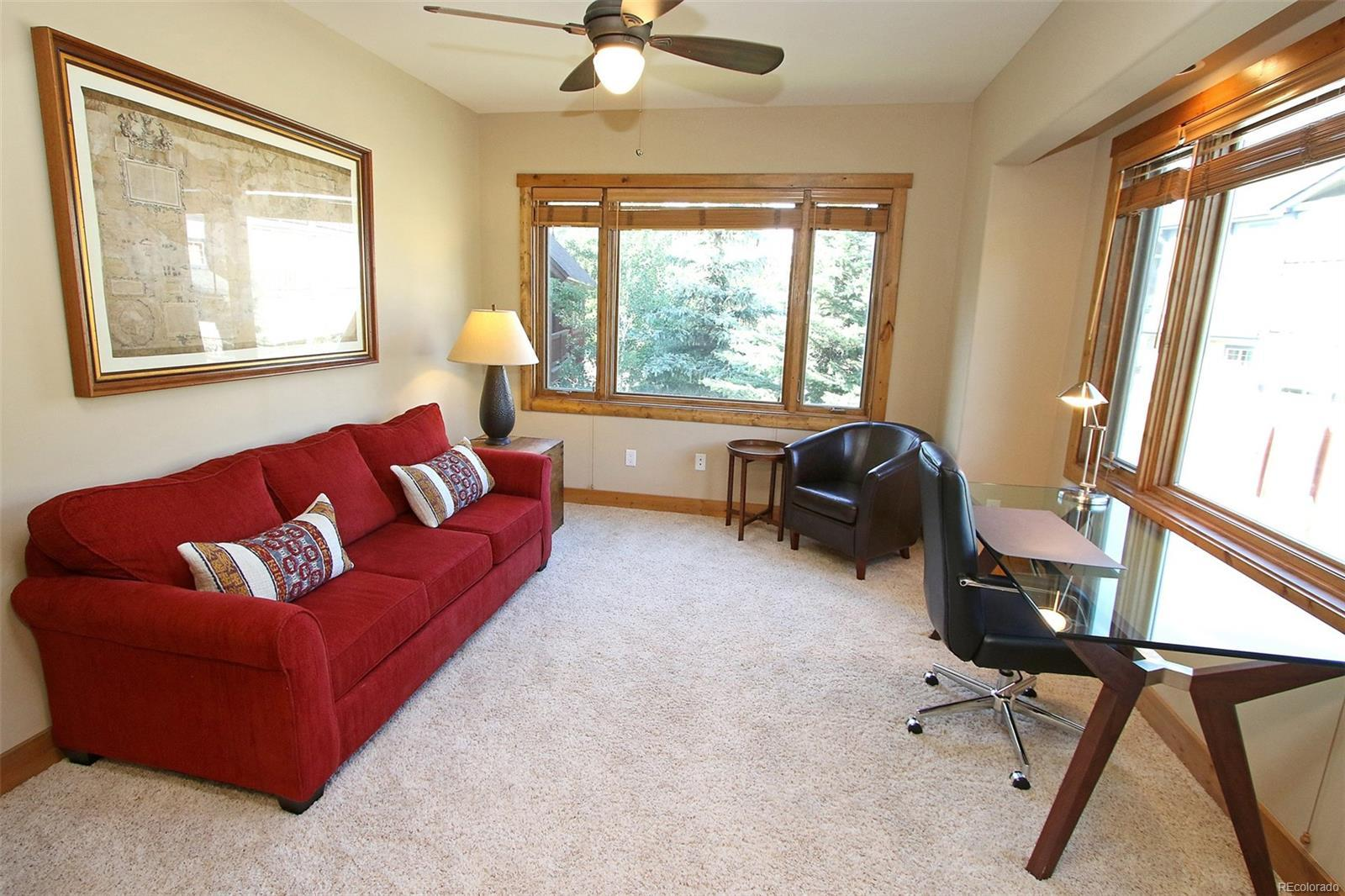 Sofa, Arm Chair, Ceiling Fan, Desk with Chair, and Windows.