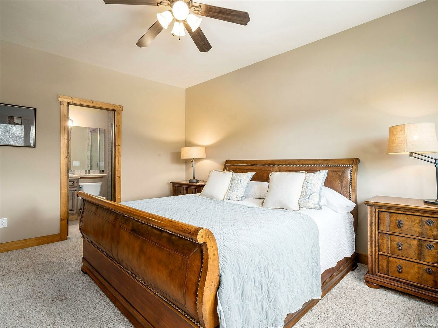 Bedroom with Bathroom, Large Bed, Nightstands, and Lamps.