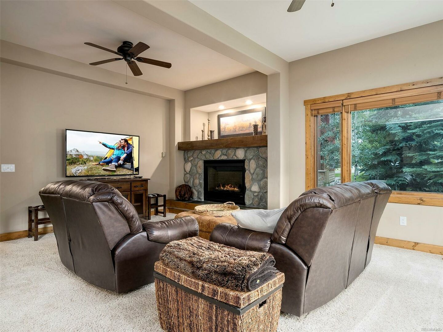 Living Area with Two Sofas, TV, Ceiling Fan, and Fireplace.