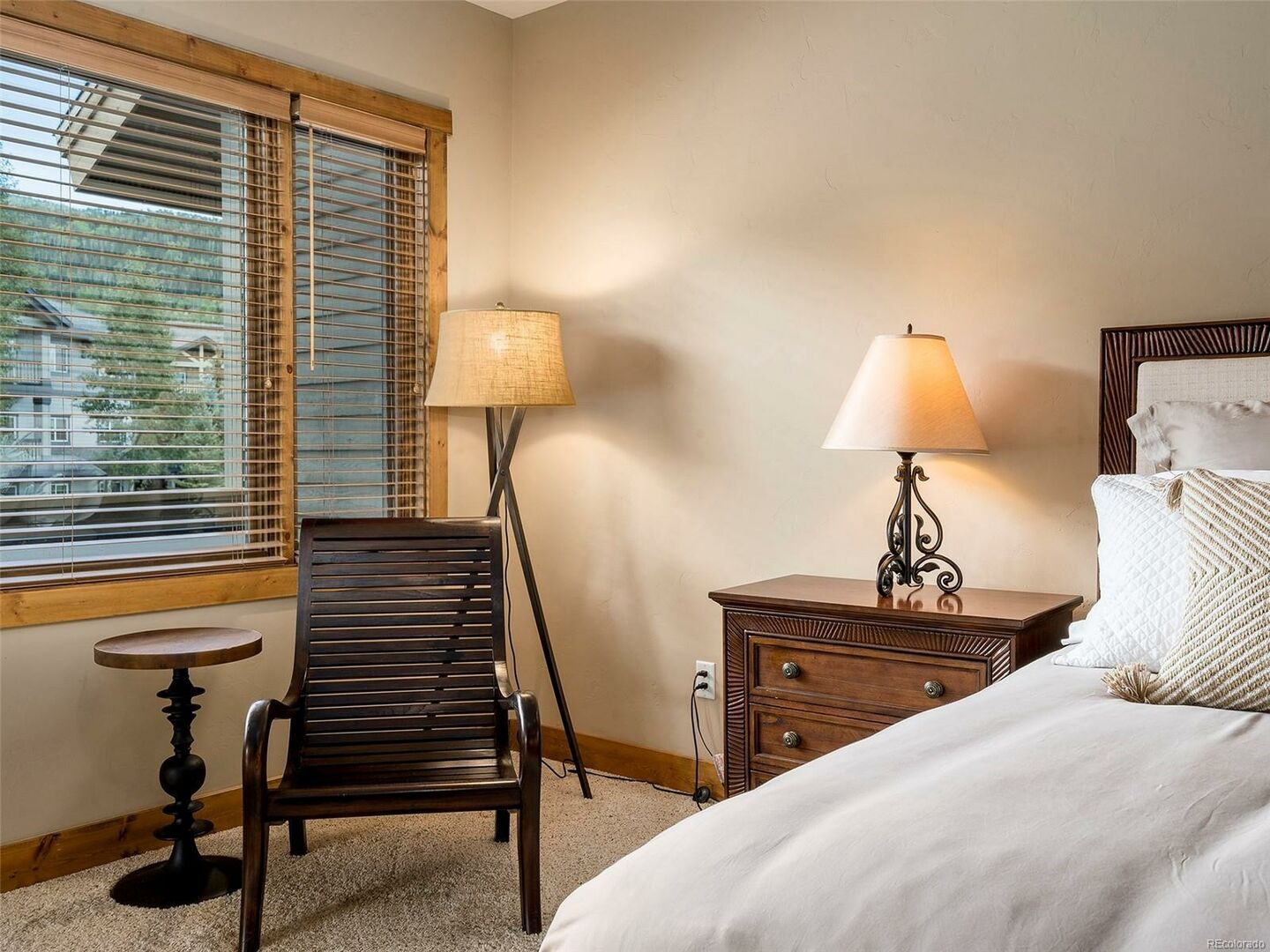 Chair, Large Bed, Nightstands, Lamps, and Window.