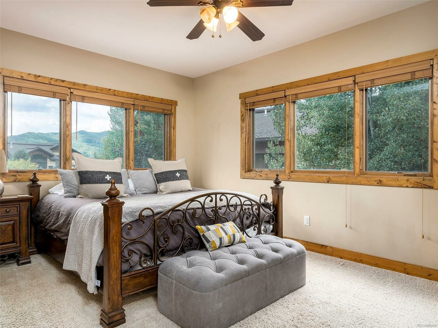 Bedroom with Large Bed, Nightstand, Ceiling Fan, and Windows.