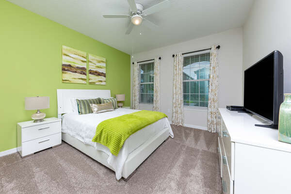 Bright and vibrant first floor bedroom featuring a TV