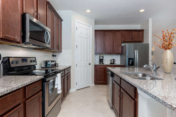 Fully-equipped kitchen with granite countertops, dark wood cabinets, and stainless steel appliances