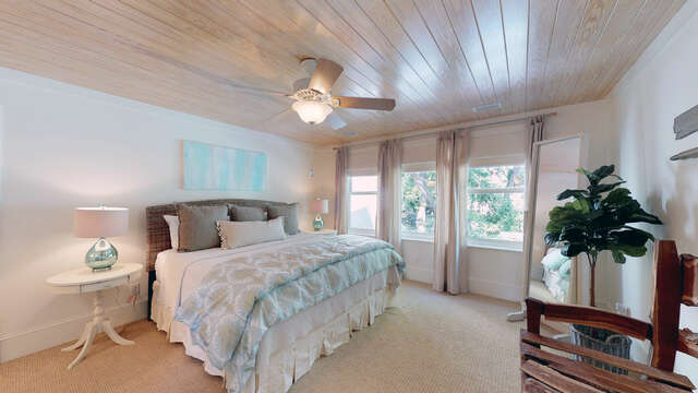 Upstairs bedroom with large bed and twin nightstands.
