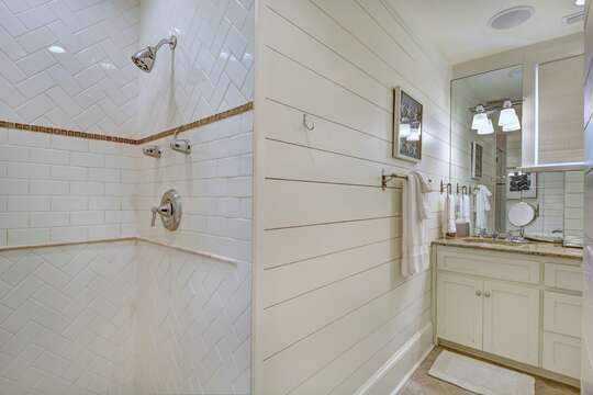 Angled photo of the master bathroom, with walk in shower and sink in shot.