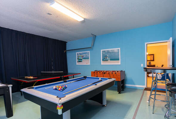 games room with pool, ping pong, foosball and air hockey and pub  style table with 2 stools