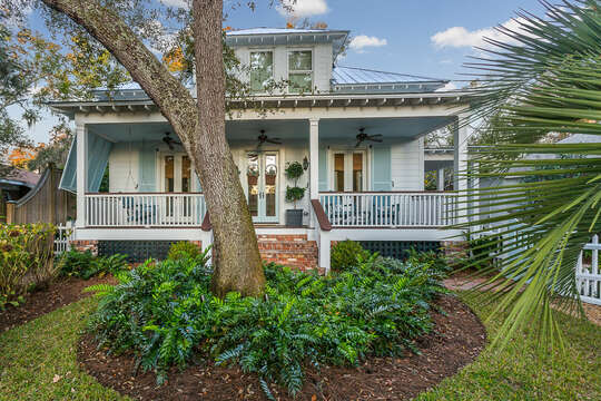 A closer photo of the front yard of this places to stay in St. Simons Island GA, with its large tree and landscaping front and center.