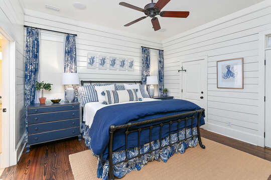 Blue bed in one of the bedrooms, with twin dressers on either side.