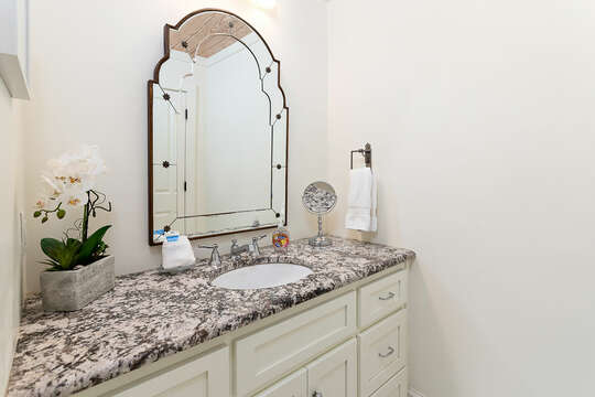 Upstairs bathroom with sink and decorative mirror.