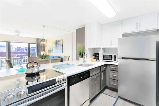Fully renovated coastal kitchen with quartz counters, stainless appliances and two toned cabinets