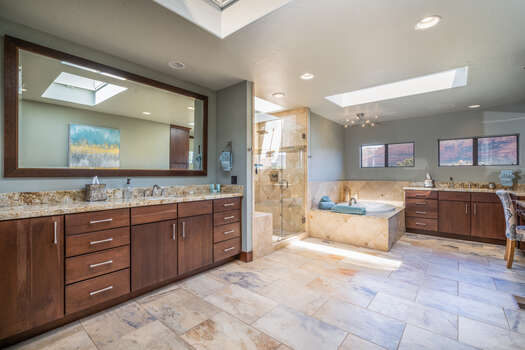 A Captivating Grand Master Bath Oasis with Stunning Tile and Granite Countertops and Dual Vanities