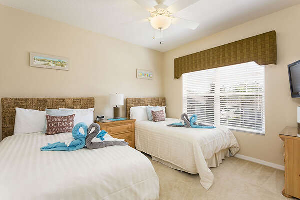 This comfortable beach themed bedroom features two full beds