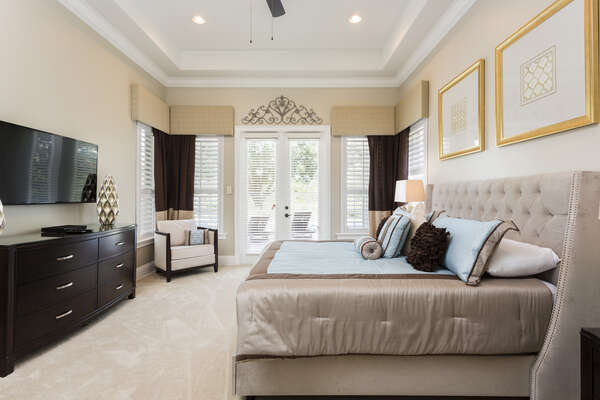 Luxury first floor master bedroom with doors leading out to the patio