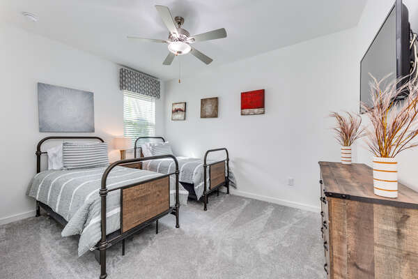 This bedroom with two twin beds is on the first floor with a shared bathroom