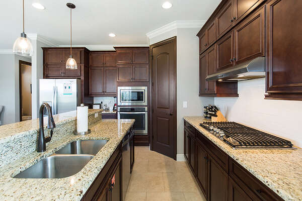 The fully-equipped kitchen features gorgeous upgraded stainless steel appliances and granite countertops
