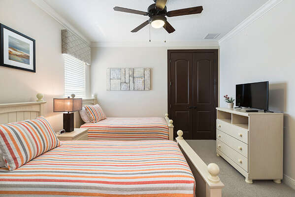 This bedroom features two twin beds, complete with a TV