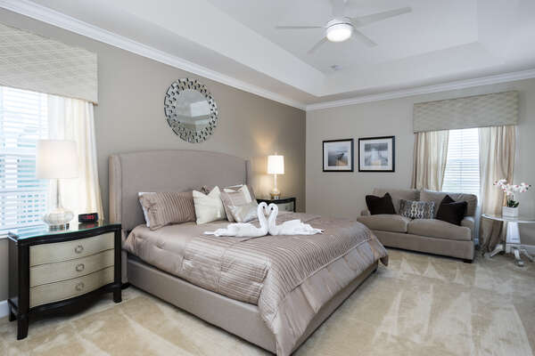 Large master bedroom that is elegantly decorated with modern grey and tan tones