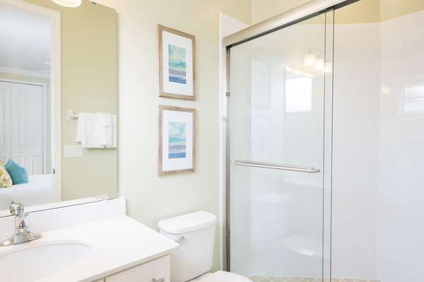 This ensuite bathroom has a glass shower and matching decor