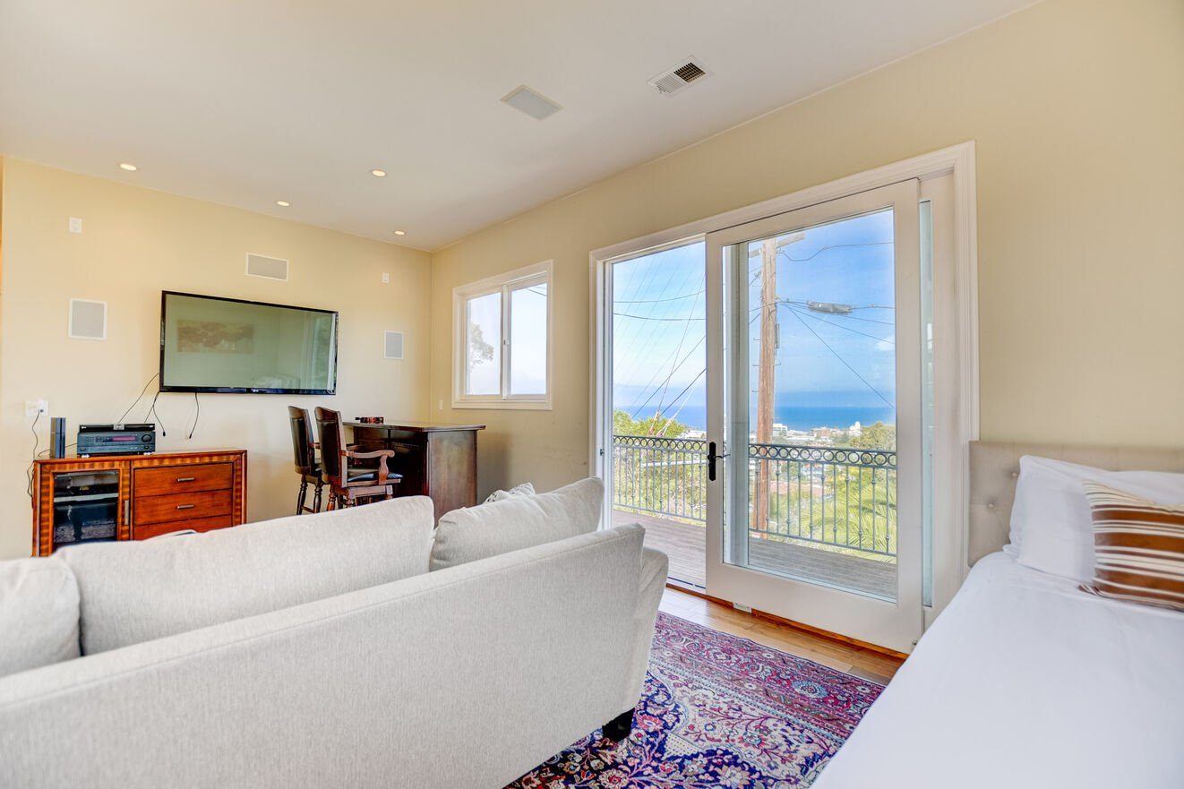 The upstairs North Wing Suite features a dedicated sitting area with Bar table and stools, flat panel TV, luxurious sofa with pull out queen size bed, balcony and ocean views